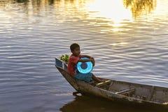 Giovane ragazzo in una canoa nel lago sap di Tonle, Cambogia Fotografia Stock Libera da Diritti