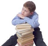 Giovane ragazzo in vestito classico che si siede con il mucchio dei libri Fotografie Stock Libere da Diritti