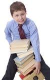Giovane ragazzo in vestito classico che si siede con il mucchio dei libri Immagine Stock