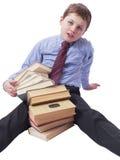 Giovane ragazzo in vestito classico che si siede con il mucchio dei libri Fotografia Stock