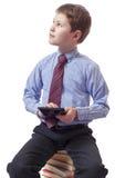 Giovane ragazzo in vestito classico che si siede sul mucchio dei libri con la compressa Fotografia Stock Libera da Diritti
