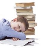 Giovane ragazzo in vestito classico che si trova con il mucchio dei libri sulle sedere bianche Fotografia Stock Libera da Diritti