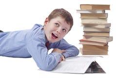 Giovane ragazzo in vestito classico che si trova con il mucchio dei libri sulle sedere bianche Fotografia Stock