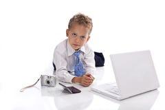 Giovane ragazzo vestito come uomo d'affari con i dispositivi Fotografia Stock Libera da Diritti