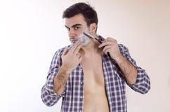 Giovane rasatura maschio con la lametta Immagine Stock