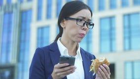 Giovane responsabile femminile che mangia hamburger non sano nella fretta, controllante le notizie sul telefono video d archivio