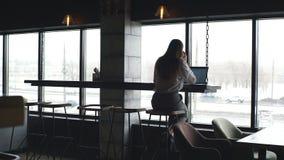 Giovane responsabile femminile sveglio che lavora con il computer portatile vicino alla grande finestra video d archivio