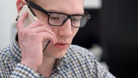 Giovane responsabile maschio che ha conversazione telefonica nell'ufficio Immagini Stock