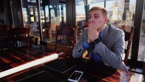 Giovane responsabile stanco che ha rottura al caffè con la carta di rotolo, la compressa e lo smartphone sulla tavola n archivi video