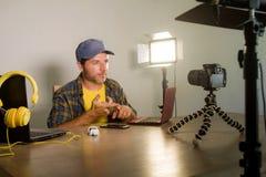 Giovane rete attraente dell'uomo del geek di tecnologia con blog della registrazione del computer portatile il video per i media  fotografie stock