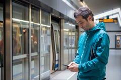 Giovane rete sociale della lettura del viaggiatore sul telefono cellulare su trasporto pubblico della metropolitana del sottopass immagini stock