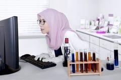 Giovane ricercatore che lavora con il computer Fotografie Stock Libere da Diritti