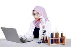 Giovane ricercatore che per mezzo del computer portatile sulla tavola Immagini Stock Libere da Diritti