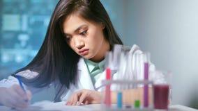 Giovane ricercatore femminile di scienza del primo piano medio durante il lavoro al laboratorio nel fondo di ciao-tecnologia video d archivio