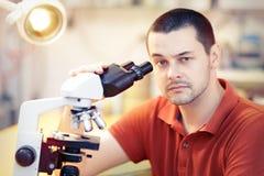Giovane ricercatore maschio scettico con il microscopio Fotografia Stock