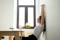Giovane rilassamento attraente della donna di affari, allungante allo scrittorio nella h Immagini Stock