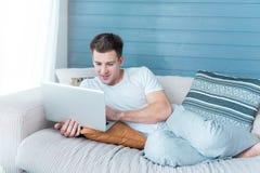 Giovane rilassato che per mezzo del computer portatile sul sofà Immagine Stock Libera da Diritti
