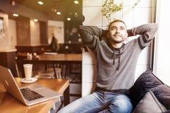 Giovane rilassato che si tiene per mano dietro la testa e che sorride mentre sedendosi alla tavola con il computer portatile in c fotografie stock