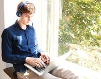 Giovane rilassato sorridente che per mezzo del computer portatile con le cuffie che si siedono sul davanzale della finestra Immagini Stock