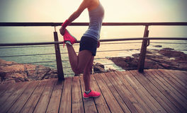 Giovane riscaldamento della donna di sport di forma fisica sulla spiaggia di alba Fotografie Stock Libere da Diritti