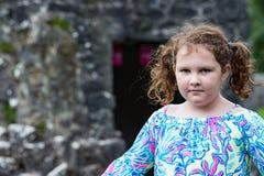Giovane ritratto della bambina che esamina la macchina fotografica con il castello di Aughnanure nel fondo Fotografie Stock Libere da Diritti