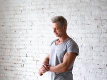 Giovane ritratto sexy dello studio dell'atleta del culturista degli uomini in sottotetto sui precedenti del muro di mattoni bianc immagini stock libere da diritti