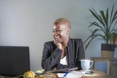 Giovane riuscita donna afroamericana nera attraente e felice nel lavoro del rivestimento di affari allegro allo scrittorio del co Fotografia Stock