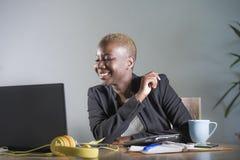 Giovane riuscita donna afroamericana nera attraente e felice nel lavoro del rivestimento di affari allegro allo scrittorio del co Fotografie Stock
