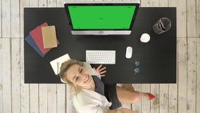 Giovane riuscita donna in vetri che si siedono alla tavola con il computer Poi guarda alla macchina fotografica e presenta un esp video d archivio