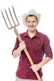 Giovane riuscito agricoltore in una camicia rossa con le forche Fotografia Stock Libera da Diritti