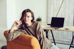 Giovane riuscito blogger o donna di affari che lavora a casa online con il computer portatile e la tazza di caffè di mattina Immagine Stock