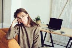 Giovane riuscito blogger o donna di affari che lavora a casa online con il computer portatile e la tazza di caffè di mattina Immagini Stock