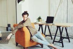 Giovane riuscito blogger o donna di affari che lavora a casa online con il computer portatile e la tazza di caffè di mattina Immagine Stock Libera da Diritti