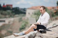 Giovane riuscito uomo che lavora al computer portatile Fotografia Stock