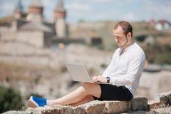 Giovane riuscito uomo che lavora al computer portatile Fotografie Stock Libere da Diritti