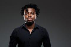 Giovane riuscito uomo d'affari africano che posa sopra il fondo scuro fotografia stock