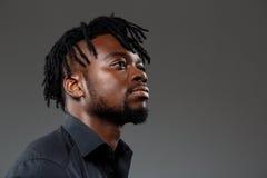 Giovane riuscito uomo d'affari africano che posa sopra il fondo scuro fotografie stock libere da diritti