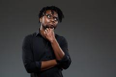 Giovane riuscito uomo d'affari africano in vetri che posano sopra il fondo scuro fotografia stock