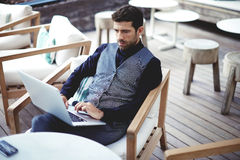 Giovane riuscito uomo d'affari che lavora ad un computer portatile mentre sedendosi in caffè durante il pranzo della pausa di lav Immagini Stock