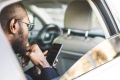 Giovane riuscito uomo d'affari che parla sul telefono che si siede nel sedile posteriore di un'automobile costosa Negoziati ed af fotografie stock
