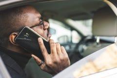 Giovane riuscito uomo d'affari che parla sul telefono che si siede nel sedile posteriore di un'automobile costosa Negoziati ed af fotografia stock