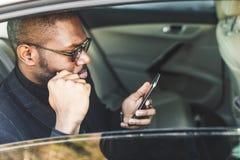 Giovane riuscito uomo d'affari che parla sul telefono che si siede nel sedile posteriore di un'automobile costosa Negoziati ed af fotografia stock libera da diritti