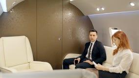 Giovane riuscito uomo d'affari ed impiegato femminile che lavorano in getto privato durante il volo archivi video
