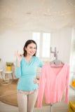 Giovane rivestimento asiatico felice della donna che cuoce a vapore i vestiti nella sala Immagine Stock