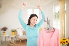 Giovane rivestimento asiatico felice della donna che cuoce a vapore i vestiti nella sala Immagini Stock