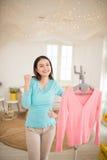 Giovane rivestimento asiatico felice della donna che cuoce a vapore i vestiti nella sala fotografia stock