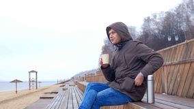 Giovane romantico che si rilassa sulla spiaggia con, sul tè o sul caffè caldo bevente dal termos Sera calma e accogliente Immagini Stock