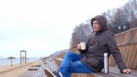 Giovane romantico che si rilassa sulla spiaggia con, sul tè o sul caffè caldo bevente dal termos Sera calma e accogliente Immagine Stock Libera da Diritti