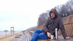 Giovane romantico che si rilassa sulla spiaggia con, sul tè o sul caffè caldo bevente dal termos Sera calma e accogliente Fotografie Stock Libere da Diritti