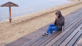 Giovane romantico che si rilassa sulla spiaggia con, sul tè o sul caffè caldo bevente dal termos Sera calma e accogliente Immagini Stock Libere da Diritti